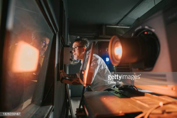 asian chinese working senior man movie operator looking through window from movie projection room backstage observing watching movie playing - film premiere stock pictures, royalty-free photos & images