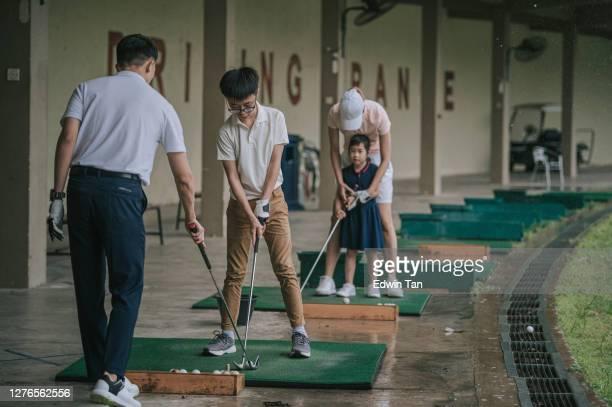 ゴルフの練習場でゴルフをしている子供たちを教えるアジアの中国の若いカップルゴルファー - ティーショット ストックフォトと画像