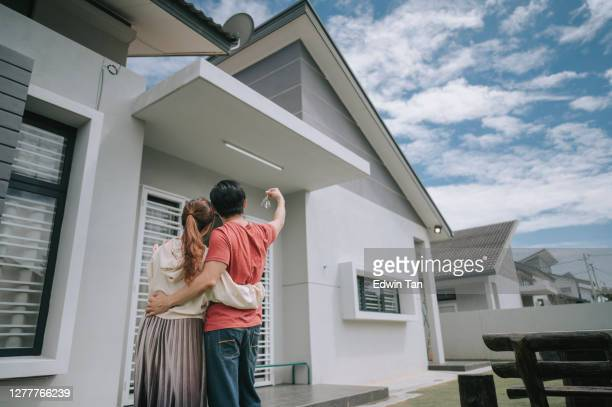 asian chinese young couple just received house key for their new house happy - australia stock pictures, royalty-free photos & images