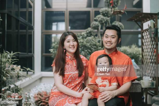 jeune famille chinoise asiatique célébrant la nouvelle année chinoise regardant l'appareil-photo retenant l'enveloppe rouge avec leur fils pour les meilleurs voeux, la chance, la prospérité et la santé - représenter photos et images de collection