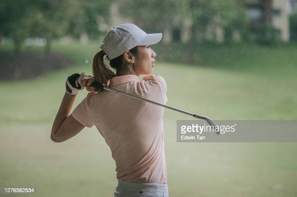 アジアの中国の若い女性ゴルファーは、雨の中でゴルフのドライビングレンジで彼女のドライバーをスイング - ゴルフ練習場 ストックフォトと画像