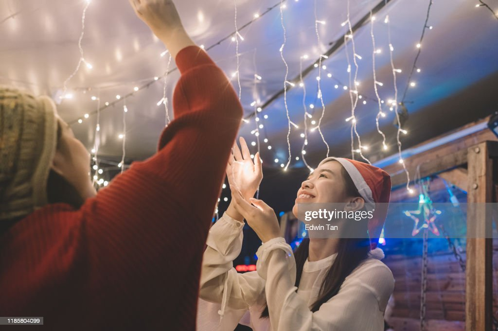 2 asian chinese young girl installing christmas string light for the party : Stock Photo