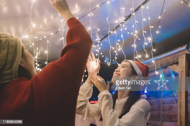 2 asian chinese young girl installing christmas string light for the party - led light stock pictures, royalty-free photos & images