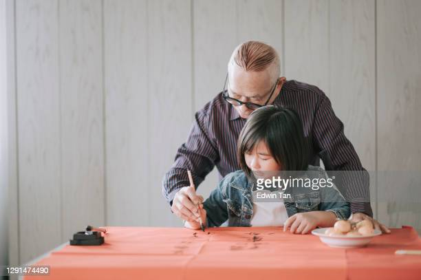 asian chinese young girl learning from her grandfather writing chinese calligraphy - chinese culture stock pictures, royalty-free photos & images