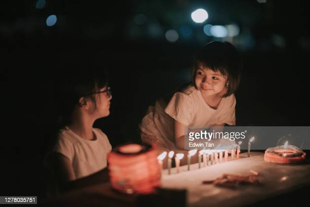 2 asian chinese young girl lighting up candle during mid autumn festival at night celebration