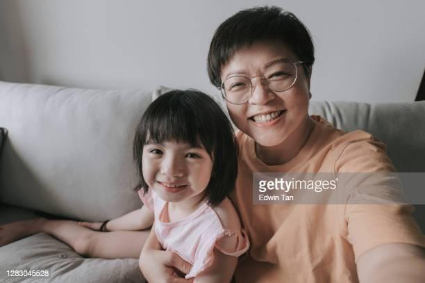 asiatische chinesische junge mädchen im gespräch mit ihrem vater mit digitalen tablet online im wohnzimmer auf dem sofa glücklich mit ihrer mutter neben - mother daughter webcam stock-fotos und bilder