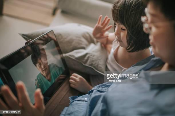 asiatische chinesische junge mädchen im gespräch mit ihrer großmutter mit digitalen tablet online im wohnzimmer auf dem sofa glücklich mit ihrer mutter neben - mother daughter webcam stock-fotos und bilder
