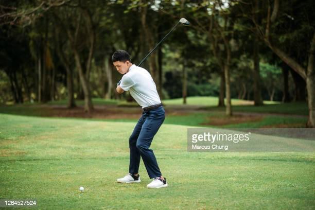 アジアの中国の若い男性ゴルファーは、ゴルフコースで彼のドライバークラブをティーオフし、スイング - ティーショット ストックフォトと画像