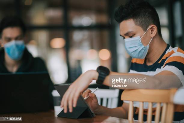 asian chinese young man using digital tablet in cafe while waiting for his coffee drink with friends - coffee drink stock pictures, royalty-free photos & images