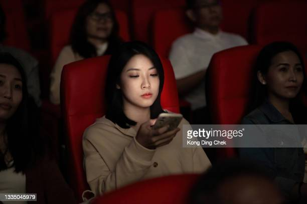 asian chinese young woman using smart phone while movie is showing in movie theater. disturbing other audience around her - film premiere stock pictures, royalty-free photos & images