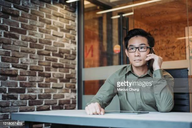 chiness asiático jovem empresário usando telefone celular e tablet digital falando em seu próprio escritório de mesa - manga longa - fotografias e filmes do acervo