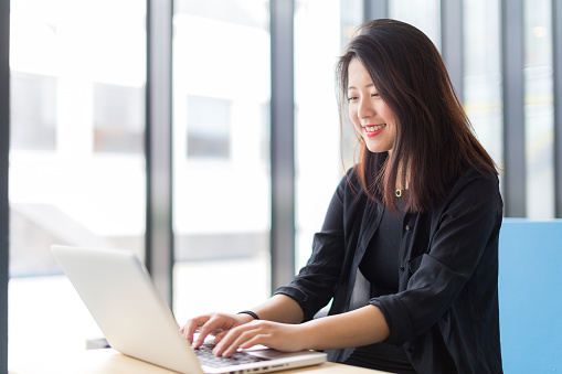 Asian college student sitting with a laptop 478949096