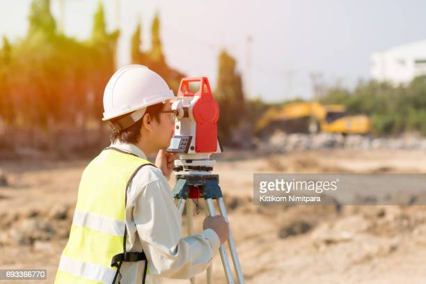 asian construction engineer checking construction site for new infrastructure construction project. photo concept for engineering work - surveyor stock photos and pictures