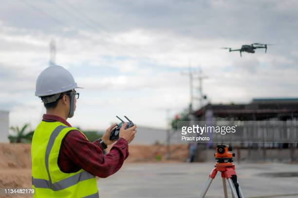 asian construction worker piloting drone at building site. video surveillance or industrial inspection - drone photos et images de collection
