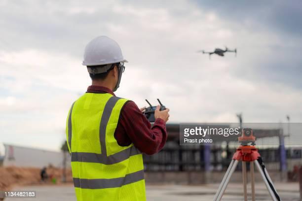 asian construction worker piloting drone at building site. video surveillance or industrial inspection - drönare transportmedel bildbanksfoton och bilder