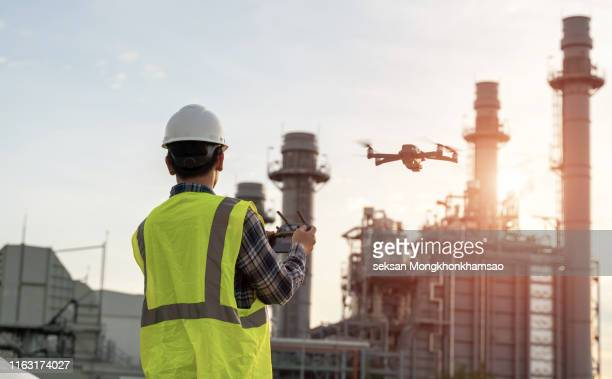 asian construction worker piloting drone at building site. video surveillance or industrial inspection - drone stock pictures, royalty-free photos & images