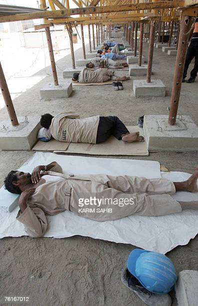 Asian construction workers rest in the shade during the midday break at a construction site in the booming Gulf emirate of Dubai 17 July 2007...