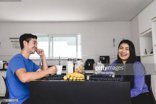oriental couple at the kitchen table for afternoon snack - sentar se imagens e fotografias de stock