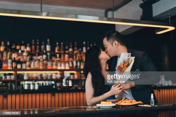 asian couple celebrating wedding anniversary or valentine's day in a restaurant - anniversary stock pictures, royalty-free photos & images
