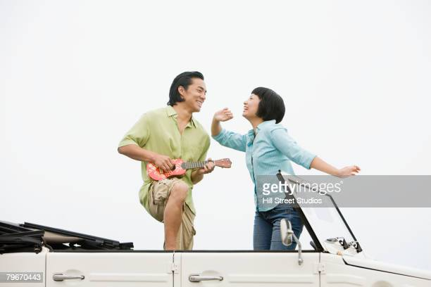 Asian couple dancing in convertible