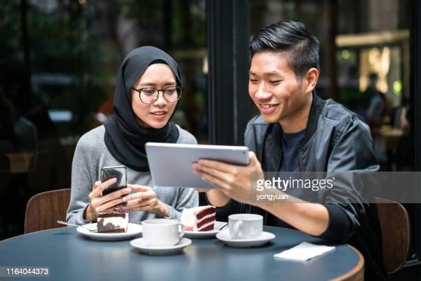 asian couple dating and using a digital tablet - muslim couple stock pictures, royalty-free photos & images