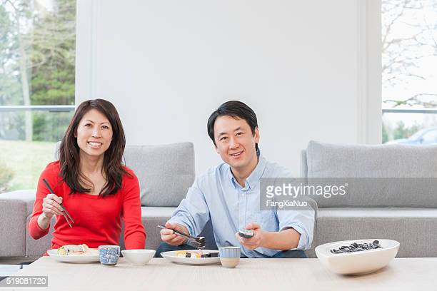 Asian couple eating at coffee table while watching TV
