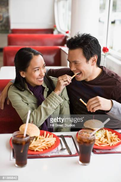 Asian couple eating at diner