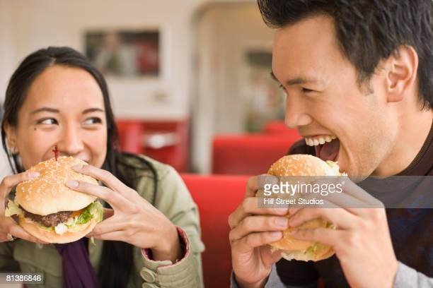 asian couple eating hamburgers - man eating woman out stock photos and pictures