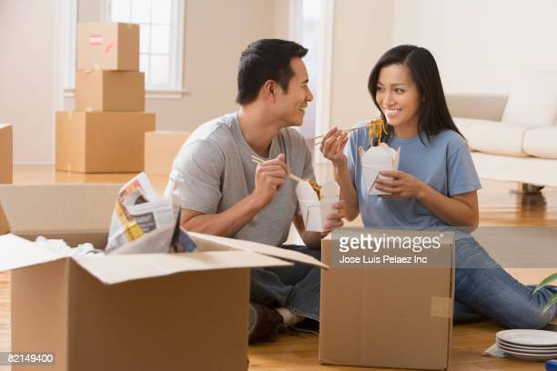 Asian couple eating take out in new house
