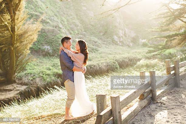 Asian couple embrace in grassy meadow