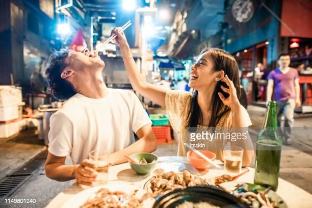 aziatisch paar genieten van straat eten in hong kong - aziatische etniciteit stockfoto's en -beelden