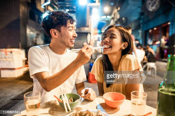 asian couple enjoying street food in hong kong - street food stock pictures, royalty-free photos & images