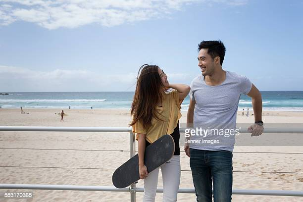 Asian couple hanging out at the beach.