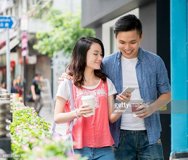 Asian couple having a cup of coffee and social networking
