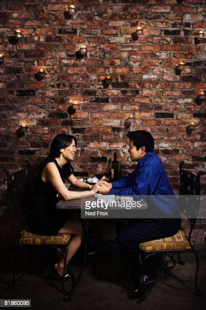 Asian couple holding hands at restaurant