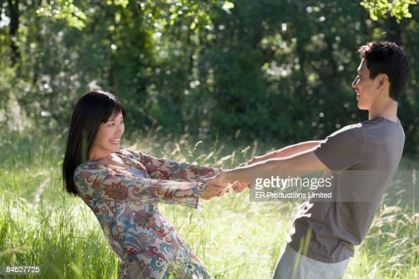 Asian couple holding hands in field