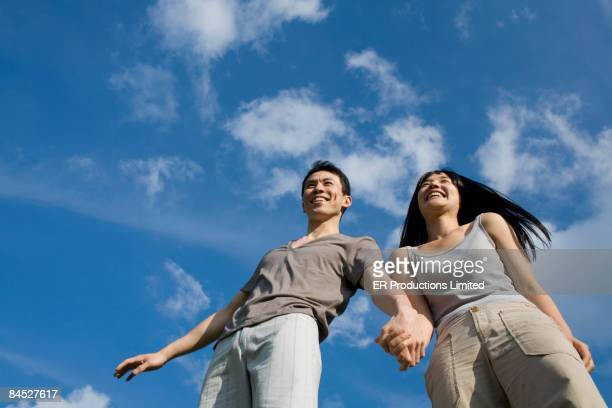 Asian couple holding hands outdoors