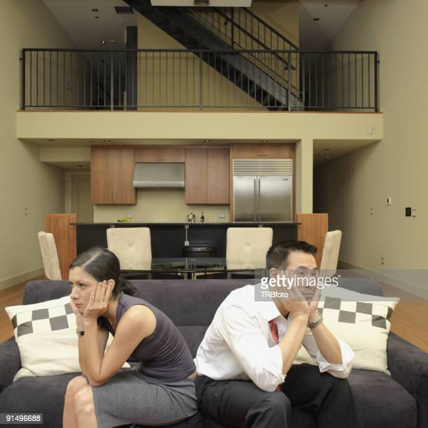 Asian couple ignoring each other on sofa