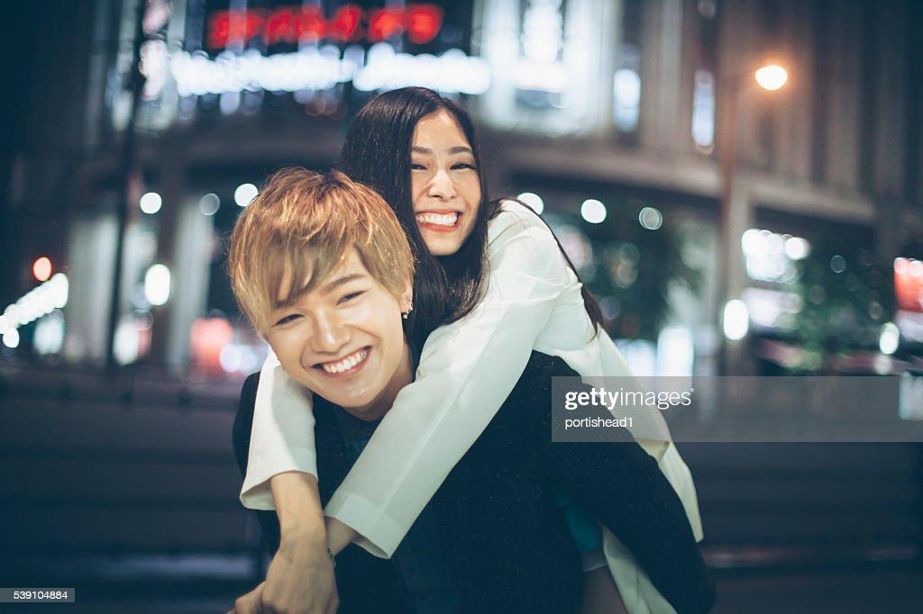 Asiatische Paar im Huckepack nehmen Sie auf der Straße bei Nacht : Stock-Foto