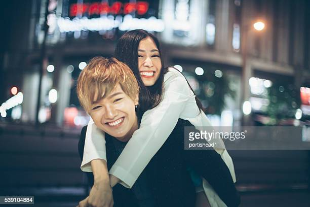 asian couple in piggyback ride on street at night - adult movies stock pictures, royalty-free photos & images