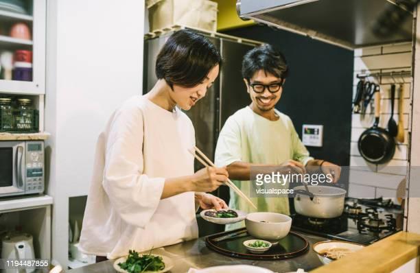 キッチンで食べ物を準備するアジアのカップル - preparing food ストックフォトと画像