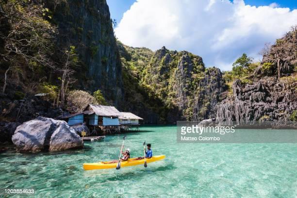 asian couple kayaking in a lagoon, coron, palawan, philippines - paisajes de filipinas fotografías e imágenes de stock