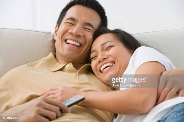 Asian couple laughing on sofa