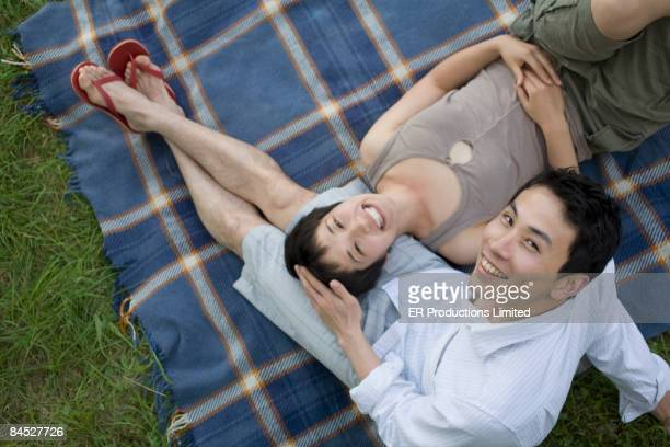 Asian couple laying on blanket in grass