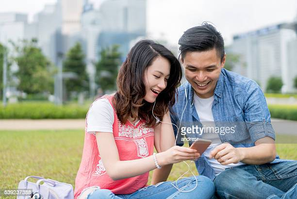 Asian couple listening to music outdoors