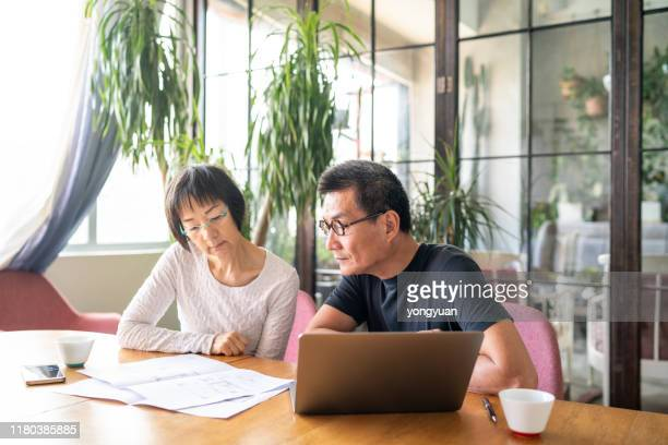 asian couple looking at blueprints of their new house - contemplation couple stock pictures, royalty-free photos & images