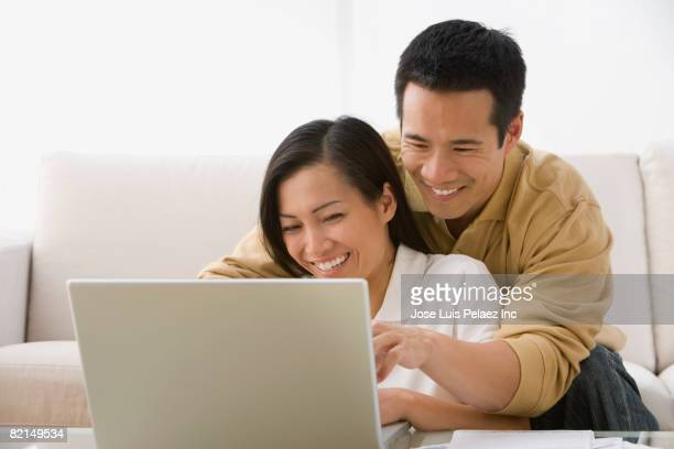 Asian couple looking at laptop
