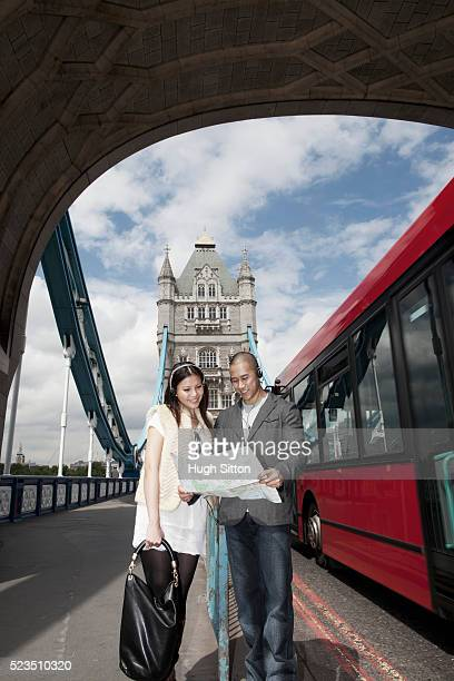asian couple looking at map, while standing on tower bridge, london, england, uk - hugh sitton stock pictures, royalty-free photos & images