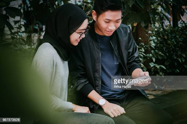 asian couple looking at phone together - rifka hayati stock pictures, royalty-free photos & images