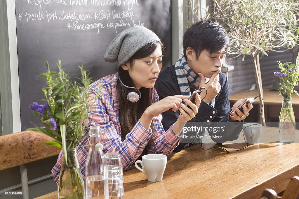 Asian couple looking at their mobile phones. : Stock Photo